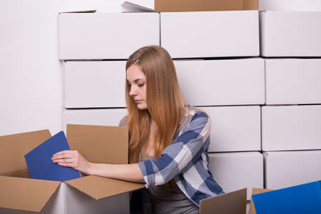 moving out: Young woman moving out and packing cardboard box