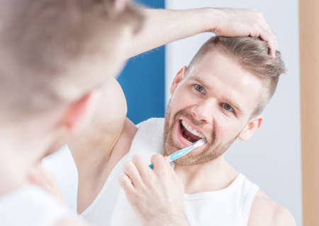 narcissism: Reflection of handsome guy brushing his teeth