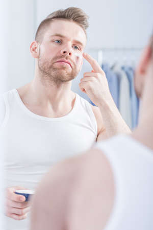 aftershave: Man caring about his skin and using face cream