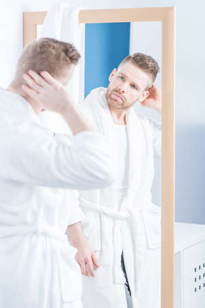 narcissistic: Narcissistic man looking in the mirror in the bathroom Stock Photo