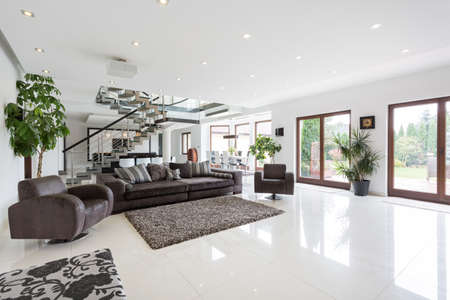 Spacious living room with staircase in residence Stockfoto