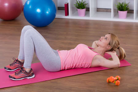 crunches: Young fit girl doing crunches on mat at home