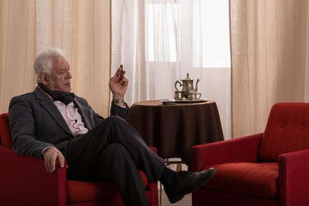 Oudere rijke man zit alleen in zijn stijlvolle lounge