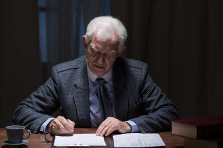Senior elegant man filling documents in his office photo