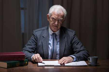 working late: Older busy man working late at night in his cabinet Stock Photo