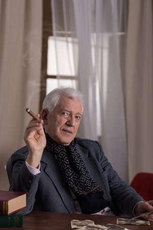 rich man: Senior rich elegant man smoking cigar alone
