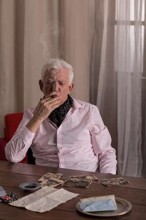 hombre fumando puro: Solitaria alto cigarro hombre de fumar y mirar fotos viejas