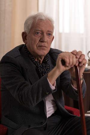 Aged sad injured man leaning on walking stick Stock Photo