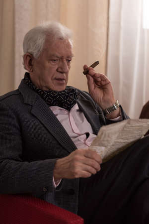 aristocrat: Senior lonely rich man with cigar reading old letter Stock Photo