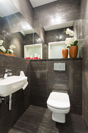 Photo of small grey marble restroom with floral decorations