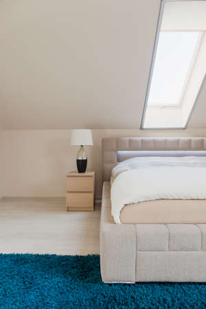 inclined: White bedroom with inclined wall and double bed Stock Photo