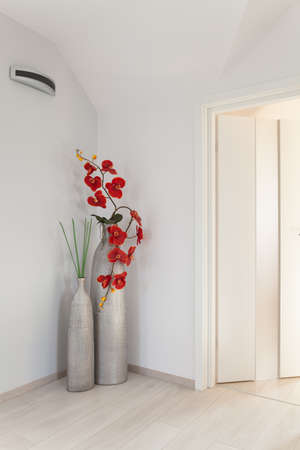 Big Silver Vase With Red Flowers In The Corner Of White Room Stock