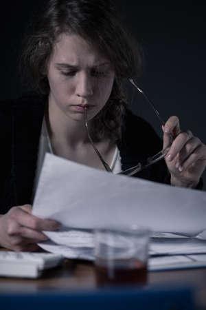 tomando alcohol: Mujer con exceso de trabajo haciendo el papeleo y el consumo de alcohol