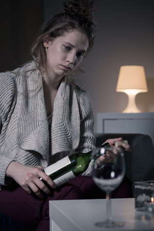 Despair young woman holding bottle of wine