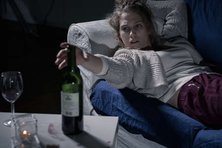 abusing: Young female alcoholic lying on the sofa