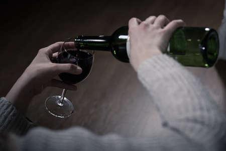 alcoholismo: Primer plano de las manos de alcohólicas verter el vino tinto
