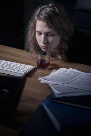 tomando alcohol: Oficinista de sexo femenino que bebe alcohol en el lugar de trabajo