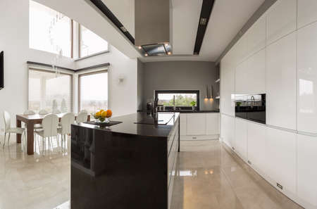 Big modern kitchen connected with spacious dining hall Archivio Fotografico