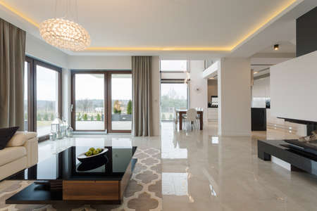 Photo of spacious expensive living room with shining marble floor Archivio Fotografico