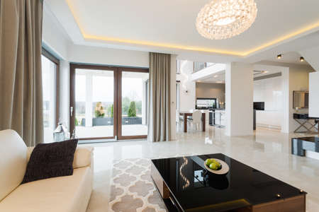 Modern decor of enormous bright lounge with fancy coffee table