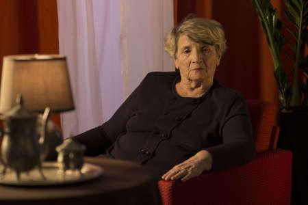 melancholic: Melancholic senior lady relaxing alone in chair