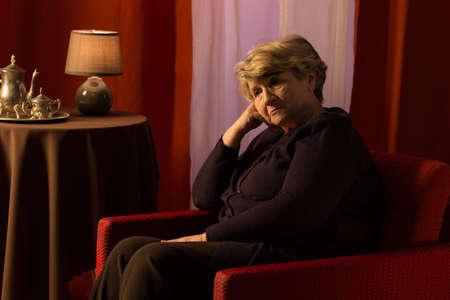 soledad: Mujer pensativa triste que se sienta en la sala de estilo vintage