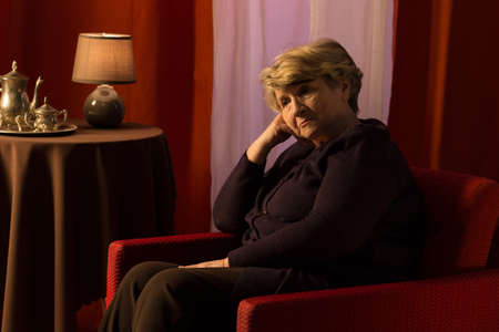 sad old woman: Thoughtful sad woman sitting in vintage style room Stock Photo