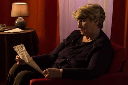 melancholijny: Elderly melancholic woman reading letter from old friend