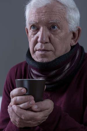 catarrh: Senior with flu holding cup of warm tea