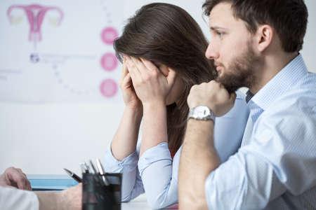 夫と婦人科医のオフィスで座っている若い女性が泣いています。 写真素材