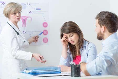 Vrouwelijke gynaecoloog uitleggen in vitro methode om verwarde vrouw