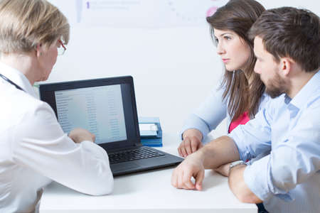 De vrouwelijke arts toont aan jonge huwelijk laboratoriumtestresultaten Stockfoto