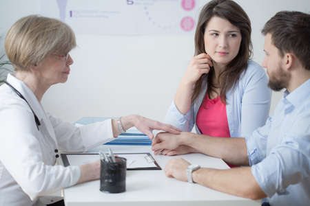 color therapy: Female supportive gynecologist and young infertile couple Stock Photo