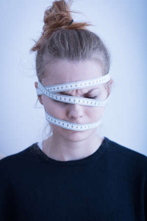 thinness: Measuring tape wrapped around the female head Stock Photo