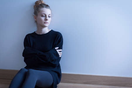 Young woman with anxiety disorder sitting on the floor Standard-Bild
