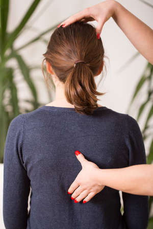 chiropractic: Therapist setting young woman in correct posture