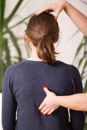 Therapist setting young woman in correct posture 版權商用圖片 - 40342824