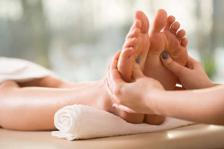 alternative wellness: Close-up of young woman having reflexology Stock Photo