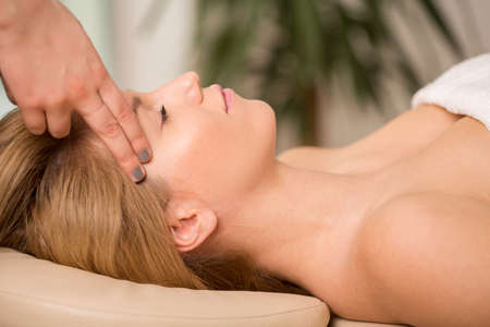 holistic: Bioenergy therapist healing young womans headache