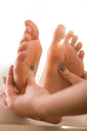 gatillo: Primer plano de terapeuta presionando los puntos gatillo en los pies de mujer