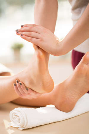 female therapist: Female therapist stretching young womans feet