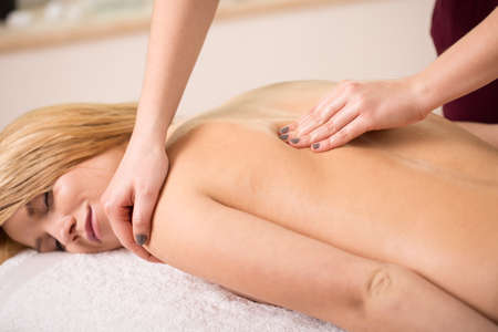 Young relaxed woman having shoulder manual therapy photo