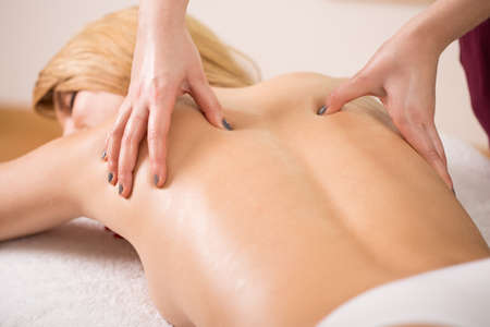 Massage therapy: Therapist pressing tight muscles on womans back Stock Photo