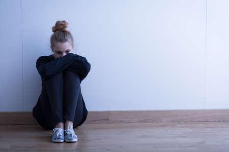 ragazza malata: Donna triste con la depressione si siede sul pavimento