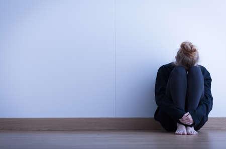 adolescente pensando: Chica sentada acurrucada en el suelo