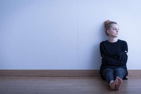 바닥에 앉아 외로운 사려 깊은 여자
