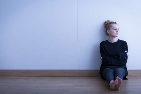 anorexia girl: Lonely thoughtful girl sitting on the floor