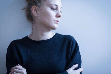 personne malade: Portrait de femme triste dans le chandail noir Banque d'images