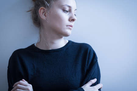 ragazza malata: Ritratto di donna triste in maglione nero Archivio Fotografico