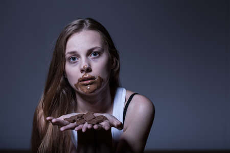 depressed person: Girl with eating disorder during bulimic attack